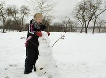 Der Junge arbeitet mit Sorgfalt sculpts einen Schneemann lizenzfreies stockbild