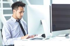 Der junge asiatische Geschäftsmann, der durch den Schreibtisch sitzt, ist Arbeit und Rest eingeschaltet stockfotografie