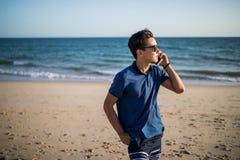 Der junge asiatische Mann, der am Telefon spricht und sehen den Sonnenuntergang auf tropischem Strand Tourist Stockfotografie