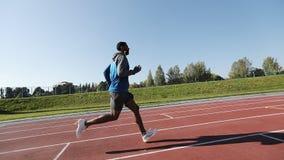 Der junge Athlet läuft schnell zum Stadion früh morgens stock footage