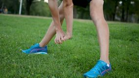 Der junge Athlet, der vor Marathon langem distane strething ist, laufen draußen auf grünem Rasen stock video footage