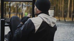 Der junge Athletenmann, der Übung auf abdominals tut, mischt Turnhalle an der im Freien im Winterpark mit stock video footage