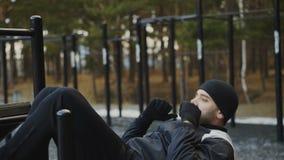 Der junge Athletenmann, der Übung auf abdominals tut, mischt Turnhalle an der im Freien im Winterpark mit stock video