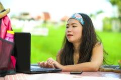 Der junge attraktive und glückliche asiatische chinesische digitale Nomade, der draußen arbeitet, entspannte sich mit Laptop-Comp Stockfotos