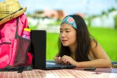 Der junge attraktive und glückliche asiatische koreanische digitale Nomade, der draußen arbeitet, entspannte sich mit Laptop-Comp Stockbild