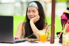 Der junge attraktive und glückliche asiatische koreanische digitale Nomade, der draußen arbeitet, entspannte sich mit Laptop-Comp Stockbilder