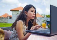 Der junge attraktive und glückliche asiatische koreanische digitale Nomade, der draußen arbeitet, entspannte sich mit Laptop-Comp Lizenzfreies Stockbild