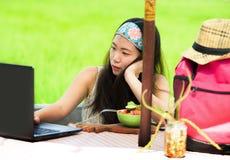 Der junge attraktive und glückliche asiatische koreanische digitale Nomade, der draußen arbeitet, entspannte sich mit Laptop-Comp Lizenzfreie Stockfotos