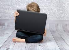 Der Junge auf dem Boden mit seinem Laptop Lizenzfreies Stockbild