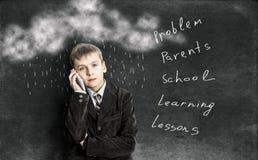 Der Junge auf dem Hintergrund der Schulbehörden mit Kreide drawin Lizenzfreies Stockfoto