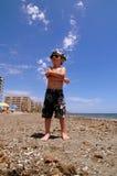 Der Junge auf einem Strand nimmt ein Sonnenbad. Lizenzfreie Stockfotografie