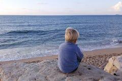 Der Junge, der auf Felsen sitzt, nähern sich der Seeuferaufwartung Lizenzfreie Stockbilder