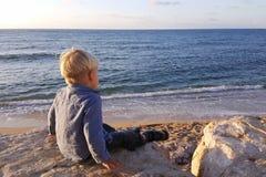 Der Junge, der auf Felsen sitzt, nähern sich der Seeuferaufwartung Stockfotos