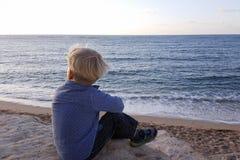 Der Junge, der auf Felsen sitzt, nähern sich der Seeuferaufwartung Stockfoto