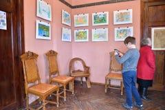 Der Junge an der Ausstellung der Zeichnungen der Kinder im Museum-e Stockfotografie