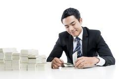 Der junge Banker zählt Banknoten auf weißem Hintergrund stockfotografie