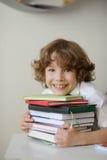 Der Junge bedrängt seinen Kastenstapel Bücher Stockbild