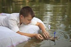 Der Junge beginnt ein Floss auf dem Fluss Stockbild