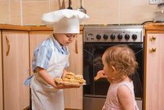 Der Junge behandelt Schwester mit Plätzchen Lizenzfreies Stockbild