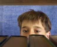 Der Junge betrachtet die Bücher Lizenzfreies Stockfoto