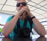 Der junge blonde Mann sitzt mit einem Rucksack an einem Tisch Stockbilder