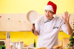 Der junge Chefehemann, der in der Küche am Weihnachtsabend arbeitet stockfotos