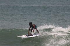 Der Junge das surfen in populären Strand Lagos, Tarkwa-Bucht, Lagos Nigeria lernen lizenzfreie stockbilder