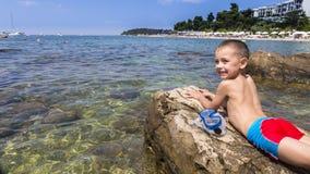 Der Junge, der auf dem Strand sich entspannt Lizenzfreie Stockbilder