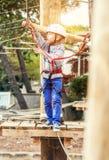 Der Junge, der auf klettert, fängt den Adrenalinepark ein Lizenzfreie Stockfotos