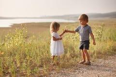 Der Junge, der Blumenstrauß des Frühlinges gibt, blüht zum glücklichen Mädchen Lizenzfreie Stockfotos