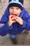 Der Junge, der einen Apfel isst Lizenzfreie Stockbilder