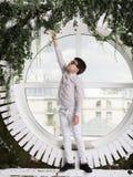 Der Junge, der im Eingang, ein rundes Fenster steht Lizenzfreie Stockbilder