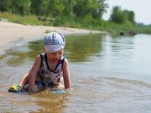 Der Junge, der im Fluss spielt Stockbild
