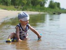 Der Junge, der im Fluss spielt Stockfotografie