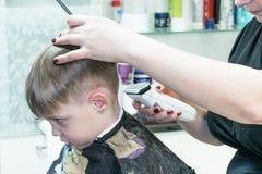 Der Junge, der im Friseursalon sitzt Es schneidet ihren Friseur Lizenzfreie Stockfotos