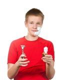 Der Junge, der Jugendliche das erste mal versucht, eine Rasur zu haben und ist konfus lizenzfreie stockfotografie