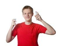 Der Junge der Jugendliche in einem roten T-Shirt mit einer Flasche in den Händen Lizenzfreie Stockfotos