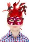 Der Junge in der Maskeradeschablone mit Federn Stockfoto
