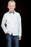 Der Junge, der mit einer Hand in der Tasche steht, lächelt Lizenzfreies Stockbild