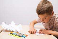 Der Junge, der Papierflugzeuge herstellt Stockfoto