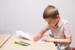 Der Junge, der Papierflugzeuge herstellt Stockfotos