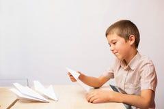 Der Junge, der Papierflugzeuge herstellt Stockfotografie
