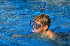 Der Junge, der in Pool schwimmt Lizenzfreie Stockfotos