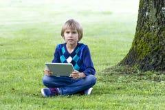 Der Junge, der unter einem großen Baum mit dem Tablet-PC sitzt Technologie, Lebensstil, Bildung, Leutekonzept Lizenzfreie Stockfotos
