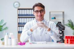 Der junge Doktor, der im Labor mit Mikroskop arbeitet Lizenzfreie Stockbilder