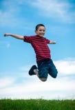Der Junge draußen springend Stockfotos