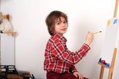 Der Junge in einem roten Hemd in einem Abschnitt zeichnet Farben auf einem Gestell Lizenzfreies Stockfoto