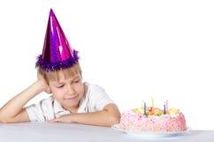 Der Junge in einer Schutzkappe mit einer Torte Lizenzfreies Stockfoto