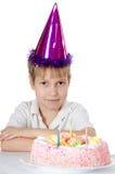 Der Junge in einer Schutzkappe mit einer Torte Stockbild