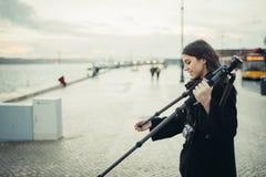 Der junge enthusiastische weibliche Fotograf, der leichten Kohlenstoffreisestativ für Sonnenuntergang-/Sonnenaufgangklotzbelichtu Lizenzfreies Stockbild